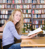 Female student reads the book in library. looking at camera — Stock Photo