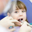 Stock fotografie: Little girl with open mouth during drilling treatment at dentist