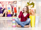 Shopping woman with bags talking on the phone. looking away and — Stock Photo