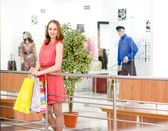 Beautiful shopping woman holding bags at a mall — Stock Photo