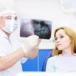 Dentist shows a patient x-ray of teeth — Stock Photo #27457437