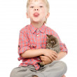 Little boy hugging a kitten showing his tongue. isolated on white — Stock Photo