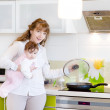 Mother with a newborn baby cook food in the kitchen — Stockfoto