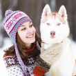 Closeup teen girl embracing cute dog in winter park — Stock Photo
