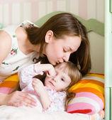 Mãe beijando uma criança doente — Fotografia Stock