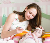 Sick kid with high fever laying in bed and mother taking temperature — Stock Photo