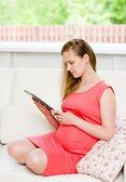 怀孕的女人坐在沙发上和使用电子平板电脑 — 图库照片
