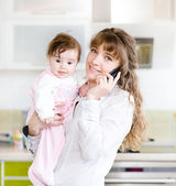 Woman on the phone while holding her baby in her arms in the kit — Stock Photo