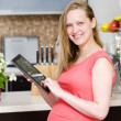 Pregnant woman using a tablet computer in kitchen — Stock Photo