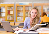 Happy student with laptop working in library. looking at camera — Stock Photo