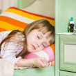 Sick girl lying on a bed — Stock Photo #29444911