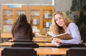 Pretty young college student in a library. — Stock Photo