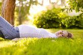 Piękna kobieta w ciąży, leżąc na trawie w słoneczny dzień — Zdjęcie stockowe