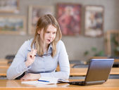 Girl using computer in a library. — Stock Photo