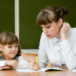 Teacher helping young girl with writing lesson — Stock Photo #29733337