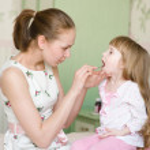 Mother examining little girl's throat — Stock Photo #29733431