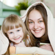 Mom and daughter having fun under the blanket — Stock Photo #29733443