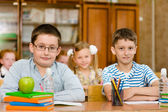 Portrait of pupils looking at camera in classroom — Stock Photo