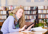 Girl using a tablet computer in a library — Stock Photo