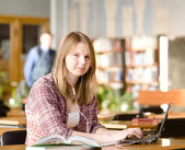 Student using computer in a library. looking at camera — Stock Photo