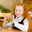 Portrait of cute schoolgirl with sandwich looking at camera in classroom — Stock Photo