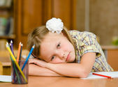 Tired schoolgirl in classroom — Stock Photo
