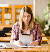 Teenage girl using electronic tablet at library — Stock Photo