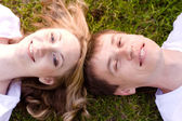 Young couple lying head to head on the grass — Stock Photo