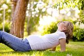 晴れた日は草の上に横たわって美しい妊娠中の女性. — ストック写真