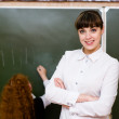 Portrait of teacher standing near blackboard — Stock Photo