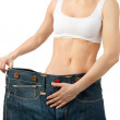 Woman shows her weight loss by wearing an old jeans, isolated on white background — Stock Photo #30672699