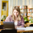 Girl using computer in a library — Stock Photo