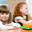 Little girl sitting and studying at school class — Stock Photo