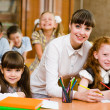Portrait of diligent schoolgirl at lesson surrounded by her class — Stock Photo