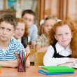 Portrait of schoolkids looking at camera at workplace — Stock Photo #30673059