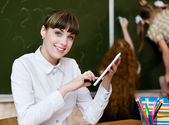 Teacher holding a tablet computer at classroom. looking at camera — Stock Photo
