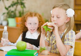 Group of classmates having lunch during break with focus on smiling girl with sandwich — Stockfoto
