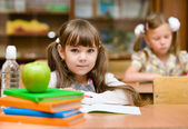 Portrait of lovely girl drawing in copybook and looking at camera — Stock Photo