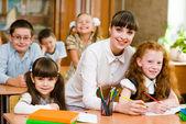 Retrato de menina diligente na lição rodeada por sua classe de — Foto Stock