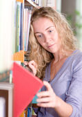Girl selecting book from a bookshelf — Stock Photo