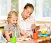 Teacher helping schoolgirl — Stock Photo
