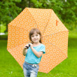 Little girl with an umbrella in park — Stock Photo