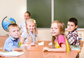 Portrait of schoolkids at workplace with teacher — Stock Photo