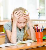 Tired schoolgirl in classroom — Stock Photo
