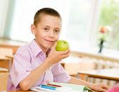 Schoolboy eating an apple — Stock Photo