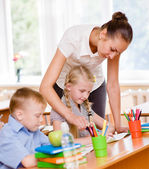 Teacher helps the schoolkids with schoolwork — Stock Photo