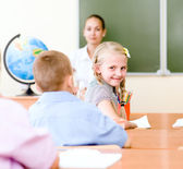Portrait of schoolgirl at workplace with teacher — Stock Photo