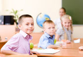 Portrait of schoolchild at workplace with teacher — Stock Photo