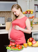 Portrait of beautiful pregnant woman holding belly in kitchen — Stock Photo