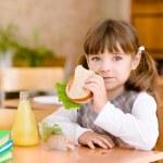 Portret schoolmeisje camera kijken terwijl het hebben van lunch — Stockfoto